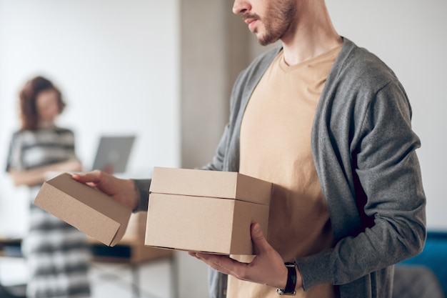 Employé de race blanche barbu avec deux boîtes en carton et son collègue avec un ordinateur portable debout au bureau de l'entreprise