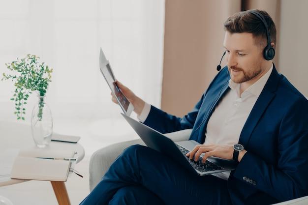 Employé responsable en costume et casque tenant des documents papier et un ordinateur portable assis dans le salon et ayant une réunion en ligne, homme d'affaires concentré travaillant à distance à la maison