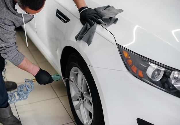 Un employé souffle et essuie la voiture après le lavage