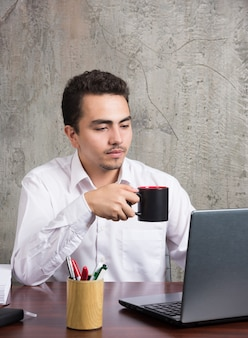 Employé tenant une tasse de thé et à la recherche d'un ordinateur portable au bureau.