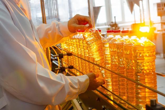 L'employé de l'usine en blouse blanche tient une bouteille d'huile dans ses mains sur un tapis roulant.