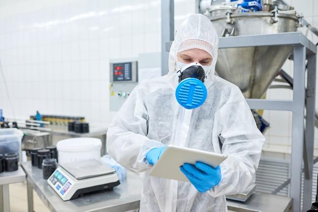 Employé d'usine debout et à l'aide de tablette