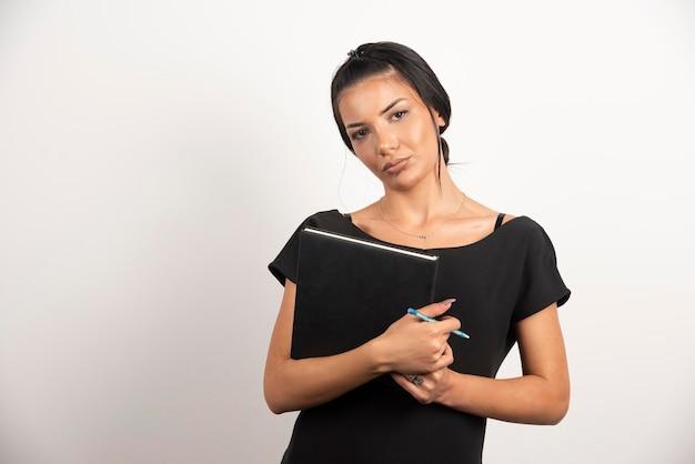 Employée brune avec ordinateur portable posant sur un mur blanc.
