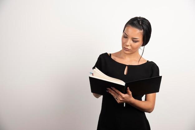 Employée brune regardant des notes sur un mur blanc.