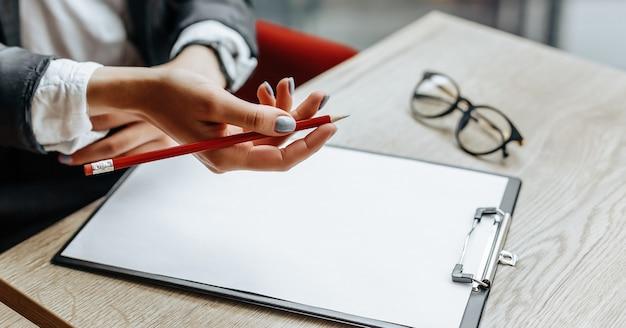 Une employée de bureau ou une femme d'affaires signe des documents. femme d'affaires concentrée travaillant avec des papiers. concept d'entreprise