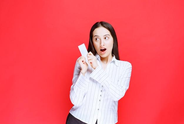 Employée de bureau montrant une carte de visite avec une expression choquée.
