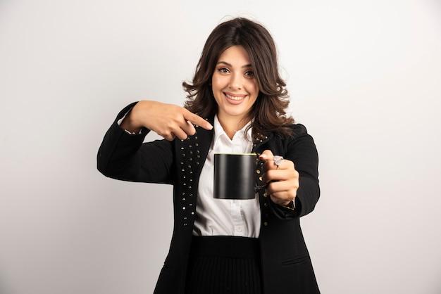 Une employée de bureau offre une tasse de thé et la montre du doigt