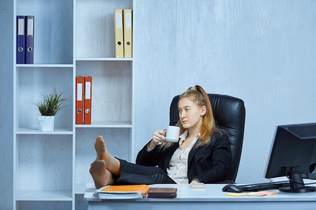 Employée de bureau prend une pause-café avec ses pieds nus sur la table
