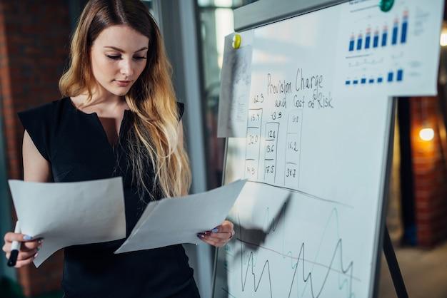 Employée de bureau travaillant sur sa présentation debout près du tableau blanc en lisant le rapport.