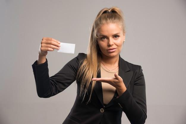 Employée en costume noir présentant sa carte de visite.