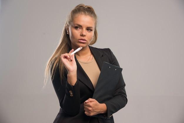Employée en costume noir tenant un contrat et a l'air réfléchie.