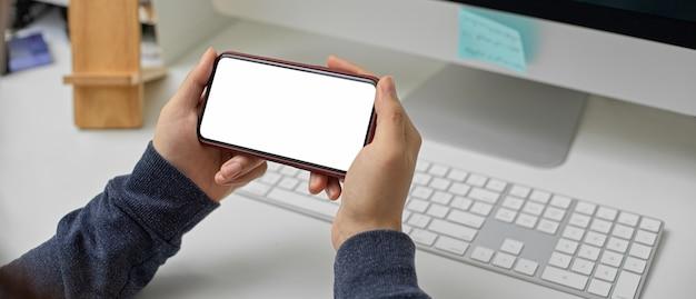 Employée de détente avec smartphone écran blanc horizontal tout en travaillant avec un ordinateur sur le bureau