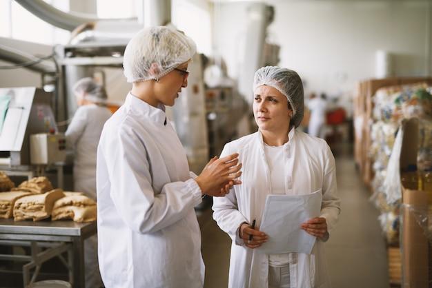 Employée dévouée concentrée dans des vêtements stériles parlant des progrès réalisés dans une usine alimentaire.