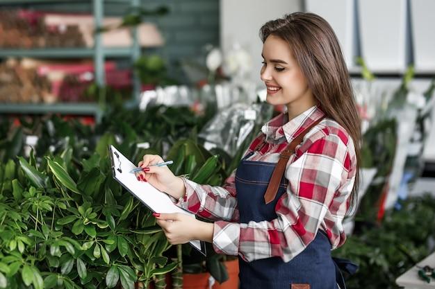 Employée du centre floral vérifiant les fleurs dans son centre moderne