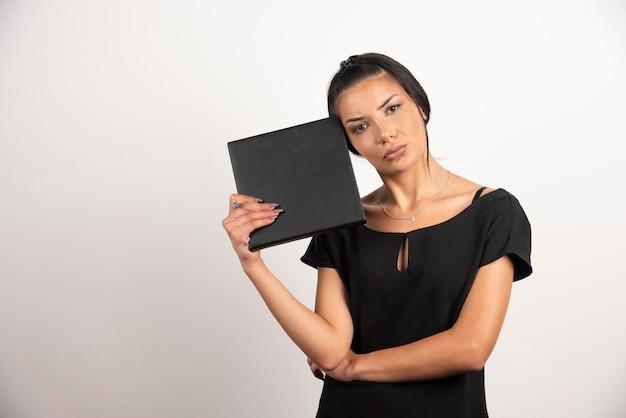 Employée épuisée avec ordinateur portable regardant la caméra.