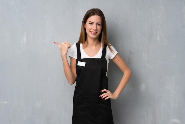 Employée femme pointant sur le côté pour présenter un produit