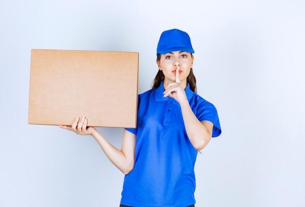 Employée de livraison avec une boîte en papier kraft montrant un signe silencieux.