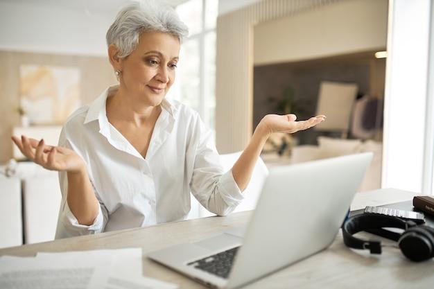 Employée mature émotionnelle en chemise blanche travaillant à domicile, assise à table avec un ordinateur portable, faisant un geste impuissant, haussant les épaules, ayant un chat virtuel en ligne
