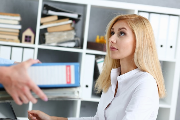 Une employée montre un paquet de documents à occupé