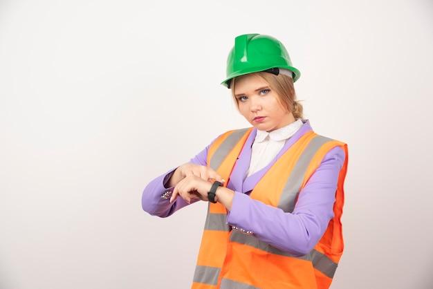 Employée de sexe féminin pointant le temps sur le mur blanc.