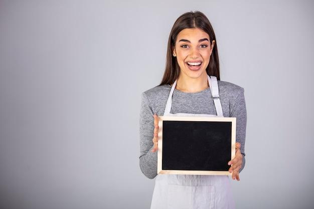 Employée de sexe féminin portant un tablier uniforme tenant une pancarte de tableau noir.