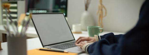 Employée travaillant sur ordinateur portable avec tasse et papeterie sur un espace de travail portable