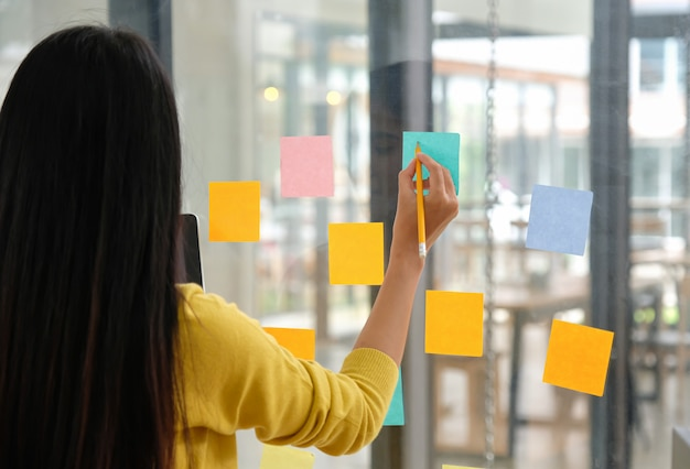 Les employées utilisent un stylo pour écrire un papernote sur le verre afin de planifier leur travail.