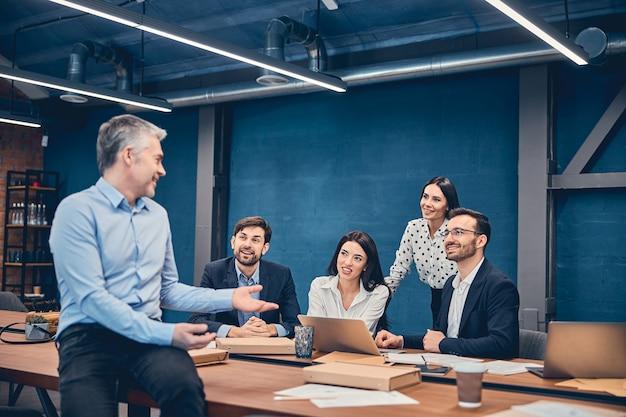 Employés assis et tenant une réunion à une grande table
