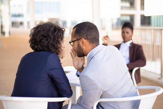 Employés bavardant au sujet d'une jeune collègue