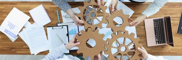 Les employés de bureau connectent les engrenages au concept de création d'équipe commerciale en place