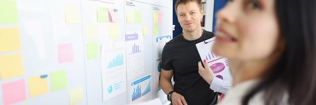 Employés de bureau discutant des chiffres d'affaires sur un tableau blanc