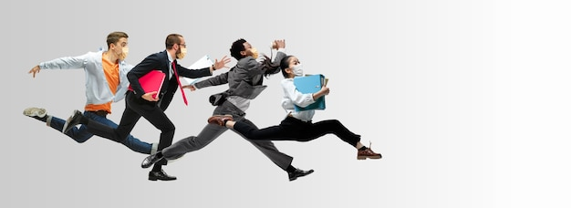 Employés de bureau heureux dans des masques faciaux sautant et dansant dans des vêtements décontractés ou un costume isolé