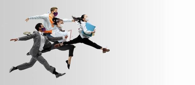 Employés de bureau heureux dans des masques faciaux sautant et dansant dans des vêtements décontractés
