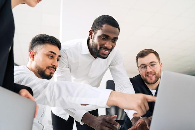 Employés de bureau multiraciaux regardant un ordinateur portable