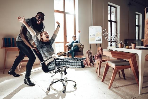 Les employés de bureau s'amusent à courir sur des chaises de bureau