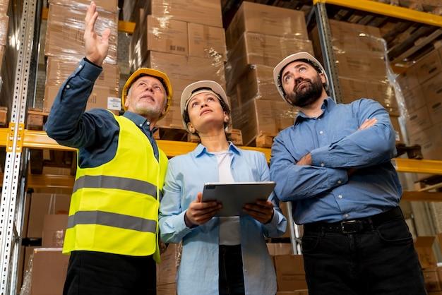 Employés avec casque travaillant dans l'entrepôt