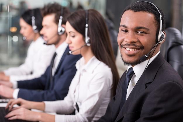 Les employés du centre d'appels sourient et travaillent sur des ordinateurs.