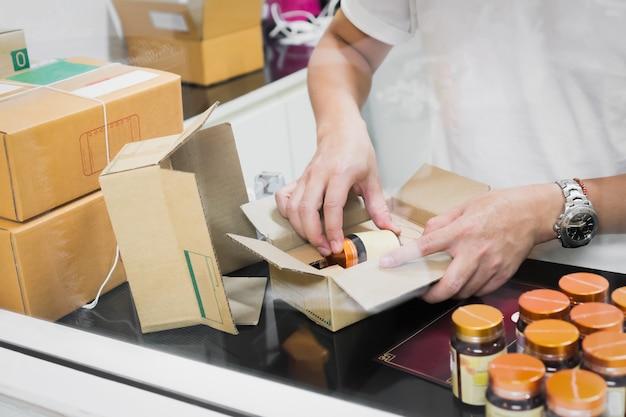 Les employés emballent un colis dans l'envoi au client.