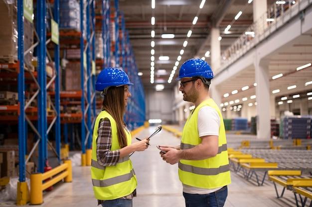 Employés d'entrepôt discutant de l'organisation