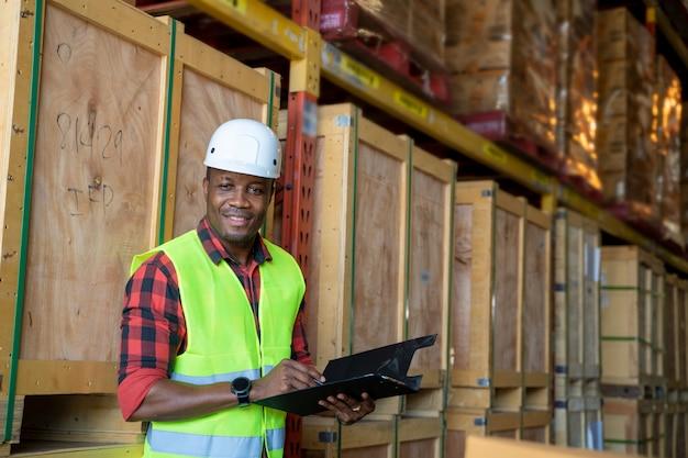 Employés d'entrepôt portrait tenant un presse-papiers travaillant dans un entrepôt.