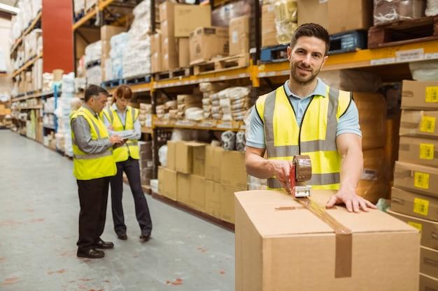 Employés d'entrepôt souriant préparant une expédition