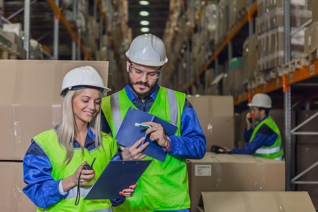 Employés d'entrepôt souriants en uniforme regardant des documents