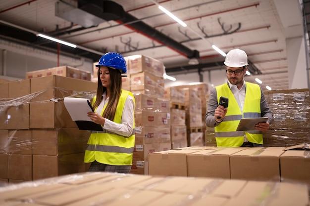 Employés d'entrepôt utilisant un lecteur de code à barres et une tablette et vérifiant l'inventaire des marchandises