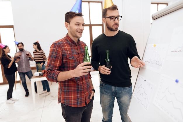 Les employés de l'entreprise parlent près d'un tableau blanc.