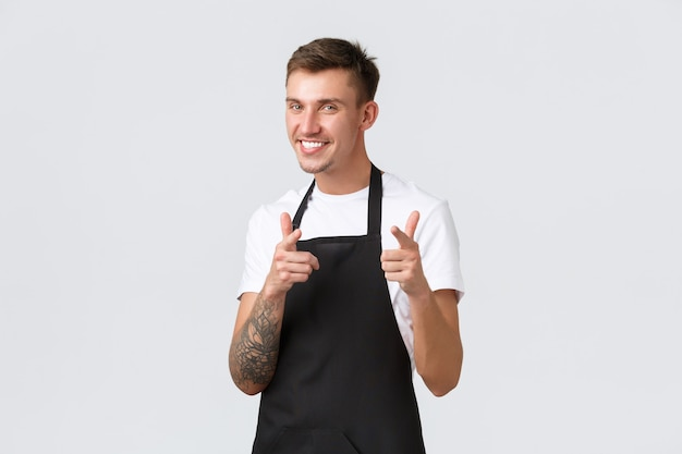 Employés, épiceries et concept de café. beau serveur blond effronté, barista en tablier noir souriant largement et pointant du doigt la caméra, invitant des invités, souhaitant la bienvenue aux clients.