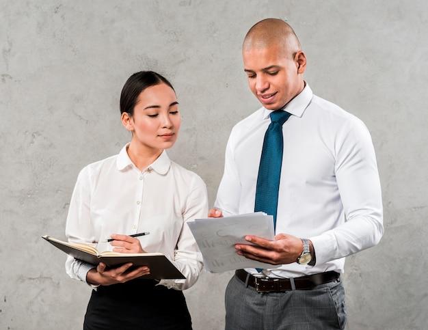 Employés de l'équipe de partenaires commerciaux discutant de documents et d'idées debout contre un mur gris