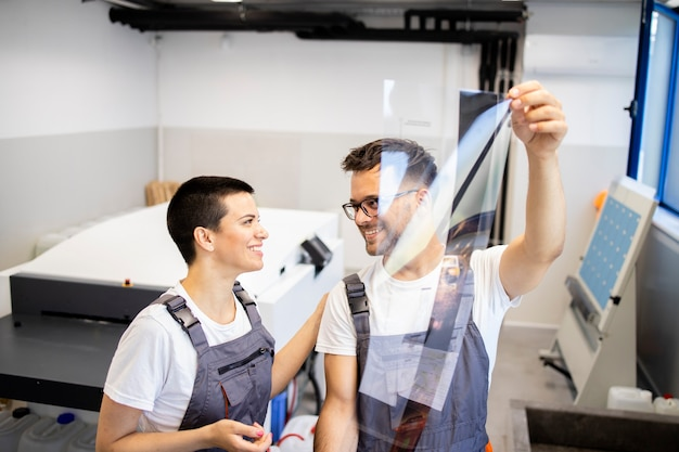 Employés d'impression analysant la mise en page de conception pour l'impression.