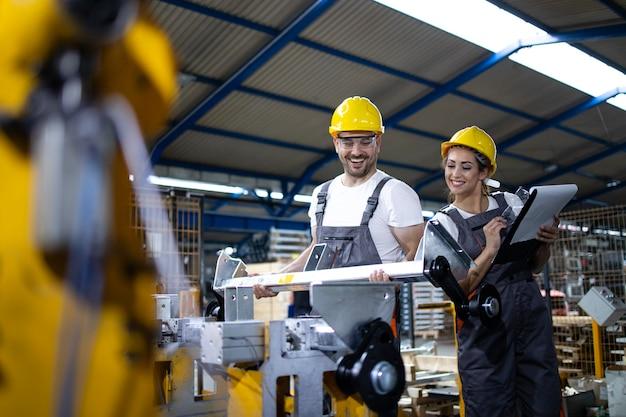 Employés industriels travaillant ensemble dans la ligne de production en usine