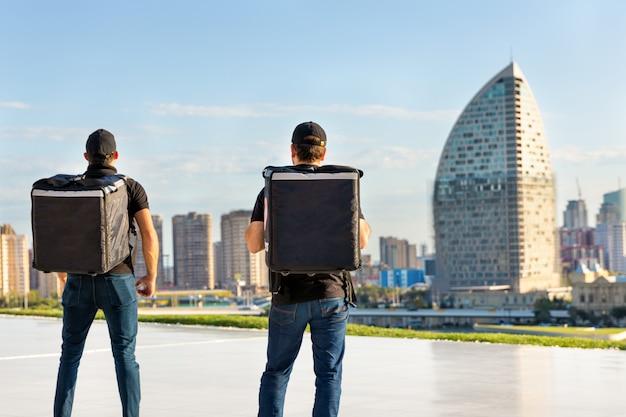 Employés de messagerie debout avec sac à dos, face à la ville
