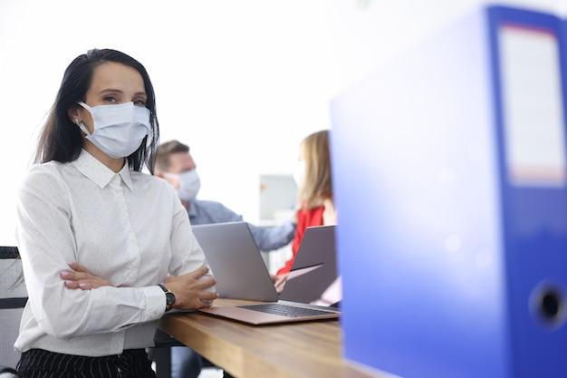 Les employés portant des masques médicaux de protection sont assis au bureau à leur bureau